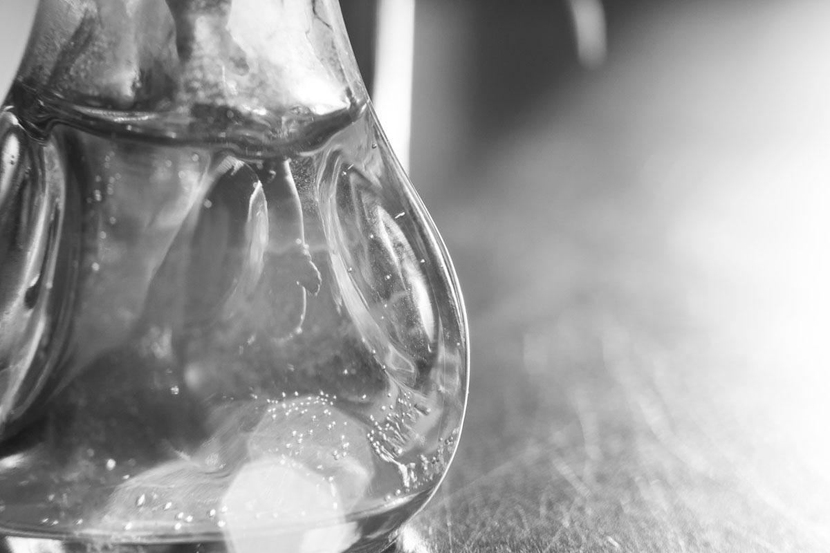 close up of sunlight through mini vase holding pothos cuttings